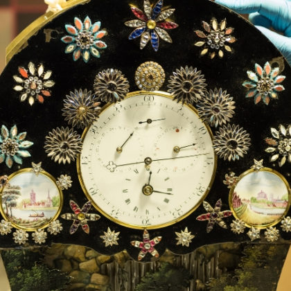 A person placing their gloved hand on a highly decorated clock.