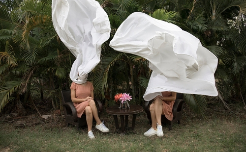 Two women sat crossed-legged either side of a table. The table is outdoors in front of some vegetation.