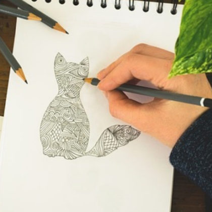 A person drawing a cat on a sketchbook.