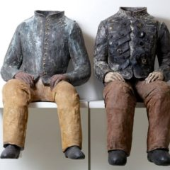 Ceramic sculptures of two headless seated men
