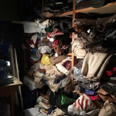Rolls of fabric on wooden shelves in dark room
