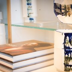 A pile of three books and a white and navy vase