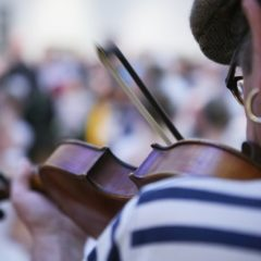 Close-up of man with earring and hat playing fiddle