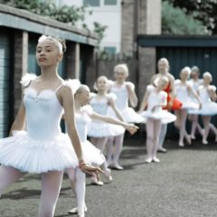 A group of young ballerinas in white tutus with relaxed poses