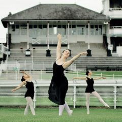 Three female ballerinas in black outfits hold poses on York Racecourse