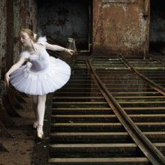 A young female ballerina with white tutu holding a pose