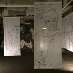 Photo of white fabric banners hung up in a dark room with drawings on