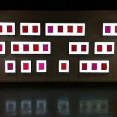 Photo of contemporary art installation - white and red light boxes against a blank wall in a dark room