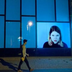 Photo of a man walking past a lit-up building with a giant image of a woman's face on it