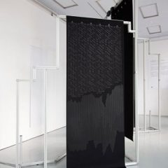 White gallery space with tall black sculpture