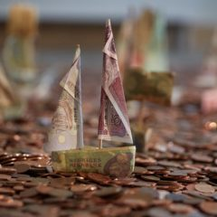 Photo of model boats on a floor of copper coins