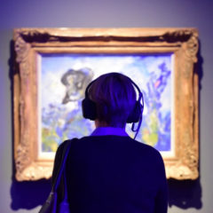 A person wearing headphones looking at a framed, blue and yellow painting.