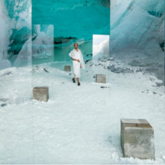 A woman walking through an art installation. The ground is covered in what looks like snow.