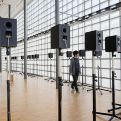 A man walking in a room of speakers.