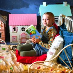 A girl sat on a bed reading Roald Dahl's 'The BFG'.