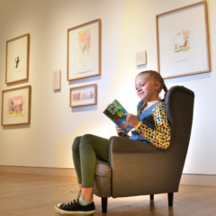 A girl reading Roald Dahl's 'The BFG' in a gallery.