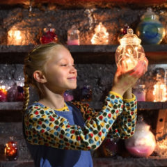 A girl holding a jar with fairy lights inside it.