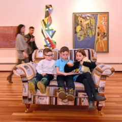 Three children sat on a sofa reading a book. Two adults are walking past the sofa.