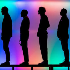 Four silhouetted people, all facing left and stood in front of a multi-coloured screen.