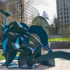 A blue sculpture in an outdoor space. The sculpture is made up of different shaped pieces.
