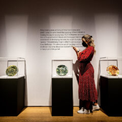 Visitor takes image of Grayson Perry ceramics in a plinth. Two other ceramics in plinths are on either end.