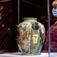 Curator Helen Walsh stands next to a Grayson Perry ceramic vase