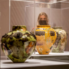 Three Grayson Perry ceramics in plinths. A visitor is in the background looking at the works.