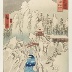 View of a snowy mountain side with a bridge over a river