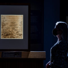 A drawings showing a landscape scene is displayed on the left. A woman stands admiring the work on the right
