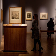 Gallery filled with drawings and paintings. A woman stands looking at a drawing on the left and in the background a woman is sat on a bench admiring a painting.