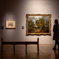 A back wall has 4 artworks displaying. two drawings on the left, followed by a large painting followed by a small drawing on the right. A woman stands admiring the painting in the foreground