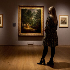 A woman stands in front of a large landscape painting with two smaller drawings on either side