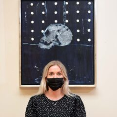 Woman stands in front of an artwork, she wears a black dress and a black mask. The artwork is a Black painting with a skull in the middle. The upper half of the work has a series of white dots. The work is framed in a silver border.