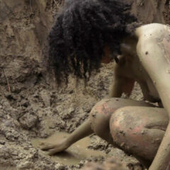 A naked woman crouched in the mud