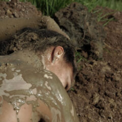 a woman lies in the mud with mud covering her naked back
